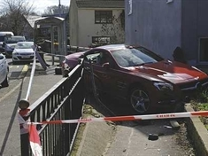 Driver arrested after car crashes through wall